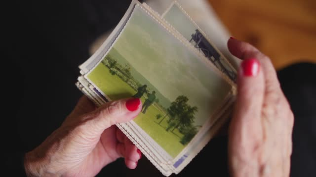 elderly woman holding old photo of her husband - the past stock videos & royalty-free footage