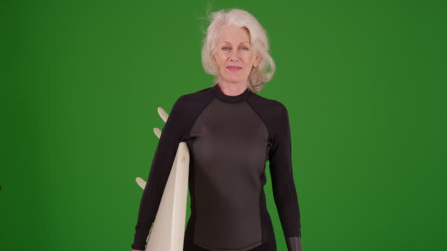 elderly woman holding surfboard looking at camera confidently on greenscreen - old diving suit stock videos and b-roll footage
