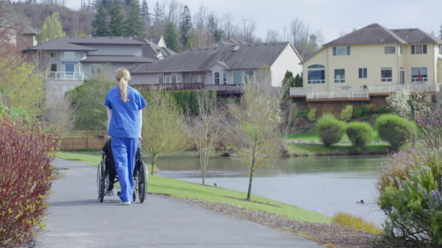 Ältere Frau im Rollstuhl zu den im Freien mit ihrer Der Fürsorgliche