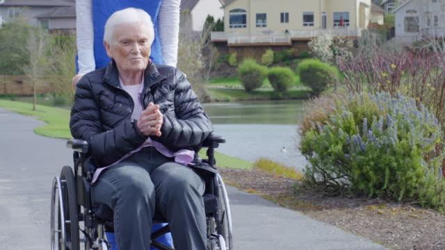 vídeos de stock e filmes b-roll de mulher idosa na cadeira de rodas a desfrutar ao ar livre com seu prestador de cuidados de saúde - bata cirúrgica