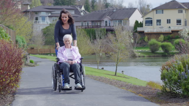 elderly woman in wheelchair enjoying the outdoors with her caregiver - wheelchair stock videos and b-roll footage