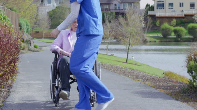 Elderly woman in wheelchair enjoying the outdoors with her caregiver