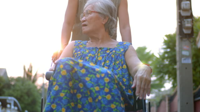 elderly woman in wheelchair with her caregiver,slow motion - pushing stock videos & royalty-free footage