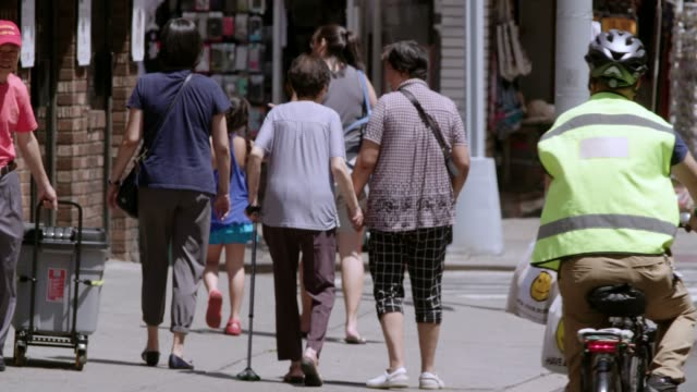 elderly woman is helped along sidewalk on a hot day in chinatown, manhattan. - a helping hand stock videos & royalty-free footage