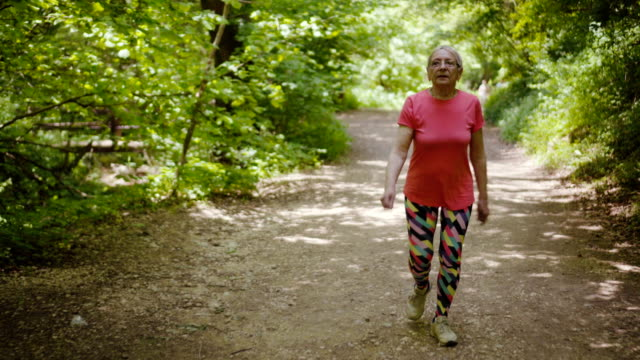 elderly woman is walking in forest - walking exercise stock videos and b-roll footage