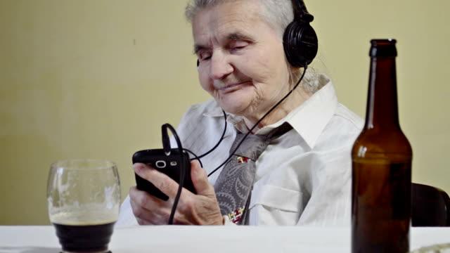 vídeos y material grabado en eventos de stock de edad avanzada mujer escuchando música en su teléfono inteligente - estéreo personal