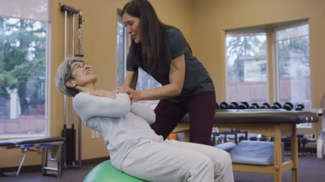 elderly woman on an exercise ball while ethnic female physical therapist assists - rehabilitation center stock videos & royalty-free footage