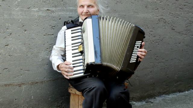 Elderly woman playing accordion.