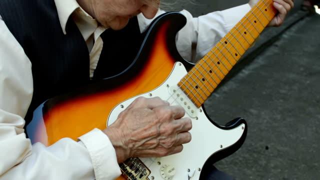 Elderly woman playing guitar.