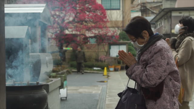 elderly woman prays at temple - japan - insel honshu stock-videos und b-roll-filmmaterial