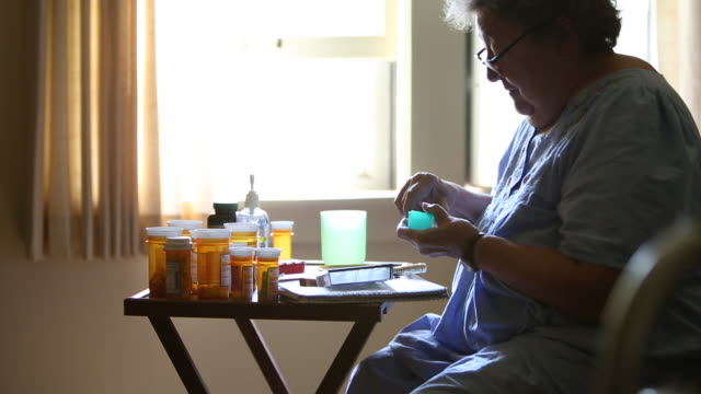 MS Elderly woman preparing to put prescription medication in pill box / Minneapolis, Minnesota, United States
