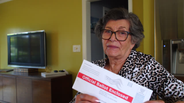 vídeos de stock e filmes b-roll de elderly woman proudly displays her absentee voter ballot - eleições