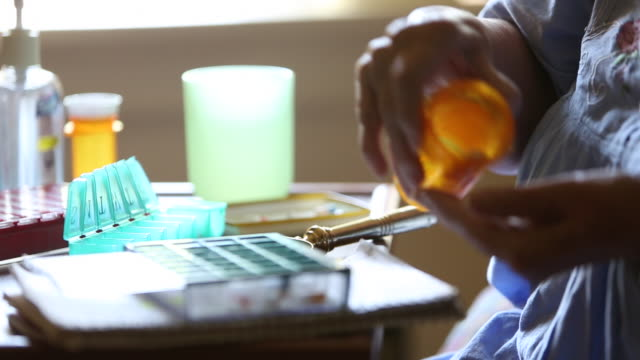 cu r/f elderly woman putting prescription medication in pill box / minneapolis, minnesota, united states - prescription medicine stock-videos und b-roll-filmmaterial