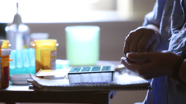CU TD Elderly woman putting prescription medication in pill box / Minneapolis, Minnesota, United States