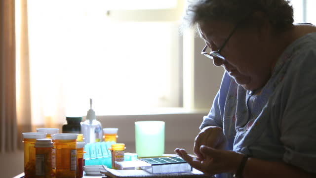 ms elderly woman putting prescription medication in pill box / minneapolis, minnesota, united states - prescription medicine stock-videos und b-roll-filmmaterial