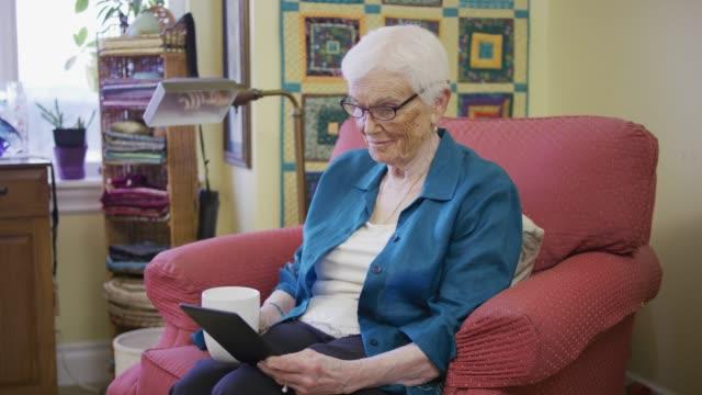 La lecture de femme âgée d'une tablette