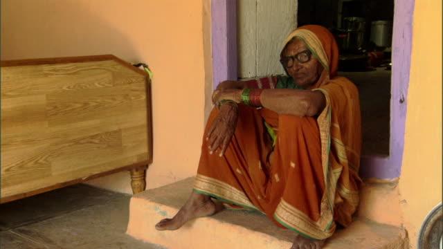 MS ZO Elderly woman seated on stoop, Pune, Maharashtra, India