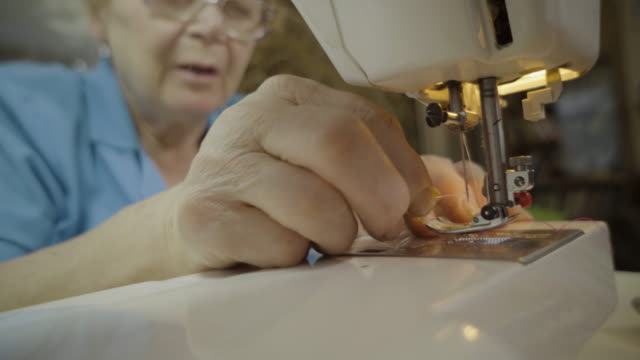 stockvideo's en b-roll-footage met elderly woman sews on a typewriter different cloths, sitting by the window in a rustic house. - werkende bejaarden