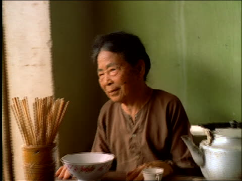 elderly woman sitting at table by window / vietnam - one senior woman only stock videos and b-roll footage