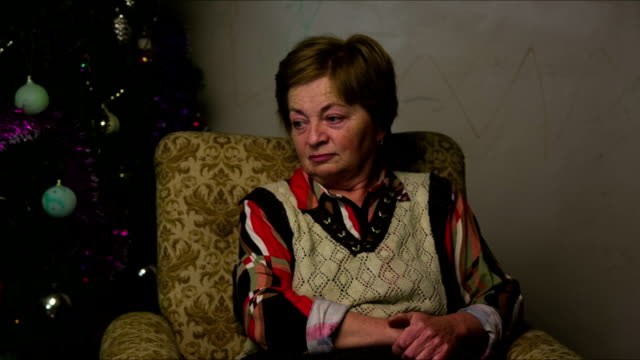elderly woman sitting in a chair on the background of christmas tree - christmas tree stock videos & royalty-free footage