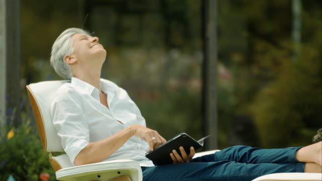 vídeos de stock, filmes e b-roll de idosos mulher sentada na leitura e jardim - previsão