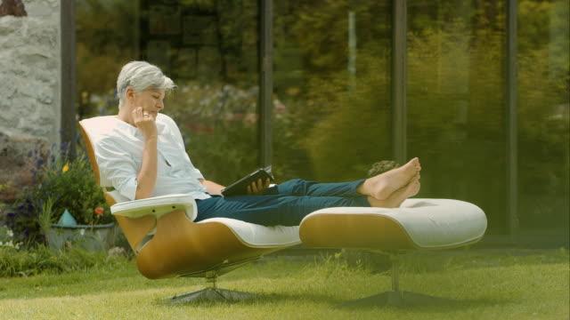 vídeos de stock, filmes e b-roll de idosos mulher sentada na leitura e jardim - old book
