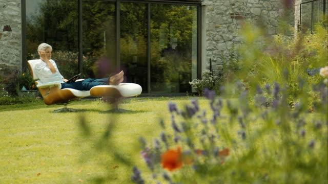 stockvideo's en b-roll-footage met elderly woman sitting in garden and reading - belgië