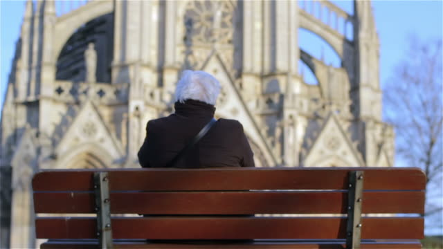 Elderly woman sitting on a bench in front of church
