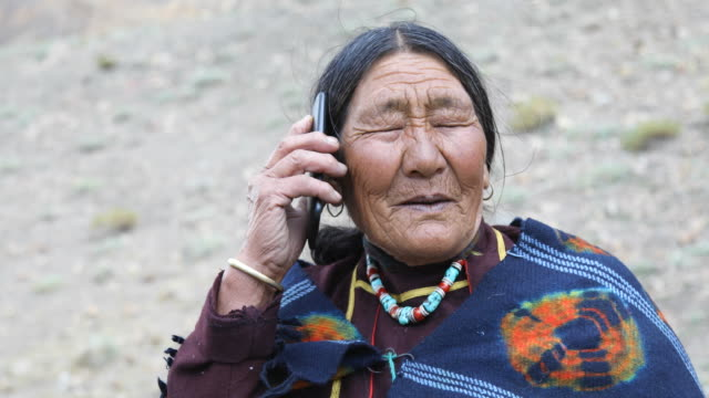 elderly woman talking on mobile phone - indigenous culture stock videos & royalty-free footage