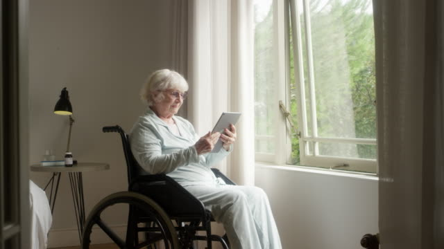 ältere frau mit tablet-pc auf rollstuhl - seniorinnen stock-videos und b-roll-filmmaterial