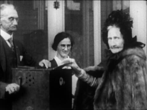 b/w 1920 elderly woman walking away from ballot box after voting / newsreel - only women stock videos & royalty-free footage