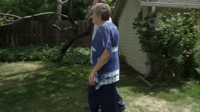 vidéos et rushes de elderly woman walking with man in backyard. man catches her when she stumbles. - trébucher