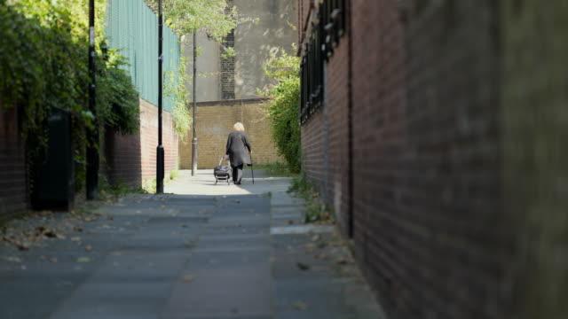 elderly woman walks down alley - fragility stock videos & royalty-free footage