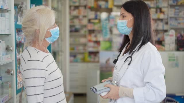 vidéos et rushes de femme âgée avec le masque facial restant dans la pharmacie et parlant et recevant des conseils du pharmacien féminin - client