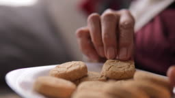 Elderly woman with plate of cookies eating delicious biscuit at home.