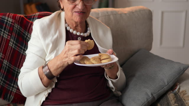 elderly woman with plate of cookies eating delicious biscuit at home. - buttermilk biscuit stock videos & royalty-free footage