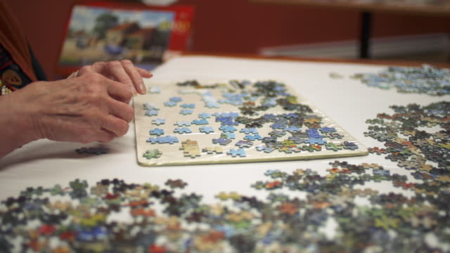 stockvideo's en b-roll-footage met elderly woman working on a jigsaw puzzle - puzzel