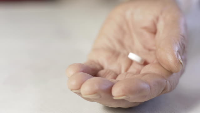 hd slow motion: elderly woman's hand with pills - capsule medicine stock videos and b-roll footage