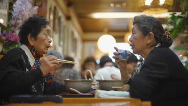 elderly women eat lunch and have conversation - Japan
