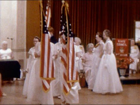 1970 elderly women in evening gowns marching with US flags around hall at state council event/ Detroit