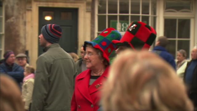 ms pan elderly women wearing funny hats at christmas market / bath, somerset, united kingdom - top hat stock videos & royalty-free footage