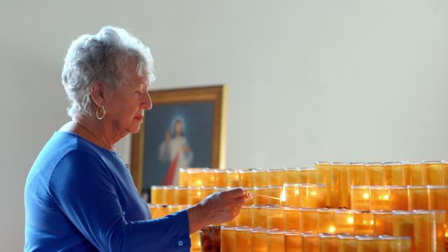 cu ts elderly worshipper in catholic church lights votive candle with a match and blows out match - votive candle stock videos and b-roll footage