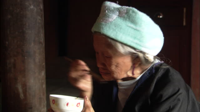 Elderly Zhuang woman eating from bowl with chopsticks, Ping'an village, Guilin, Guangxi Zhuang