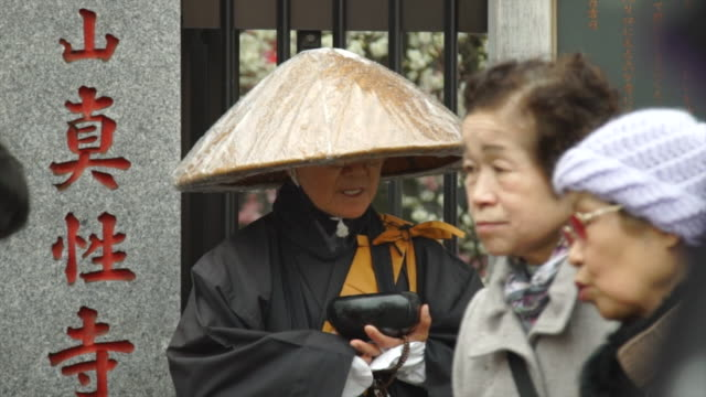 eldrly woman stands in silence at temple - Japan