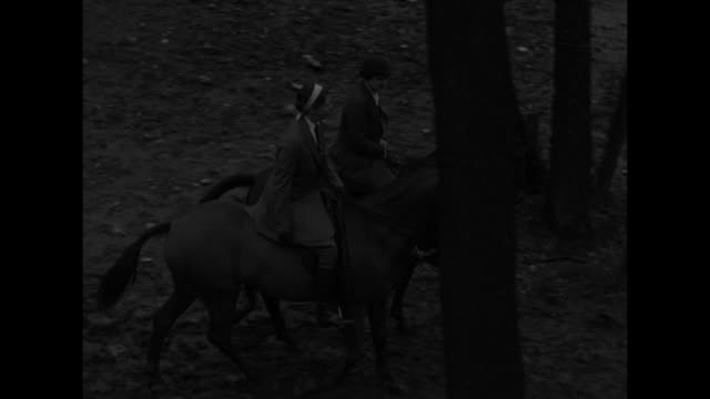 MS Eleanor Roosevelt and Elinor Morgenthau ride horseback through wooded river area over small bridge/ MS Roosevelt waves to camera with Morgenthau /...