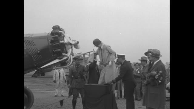Eleanor Roosevelt wife of NY Gov Franklin D Roosevelt standing on platform in front of plane she breaks bottle of champagne on plane's propeller...