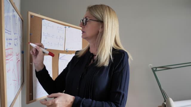 e-learning professor writing formulas on white board - professore video stock e b–roll