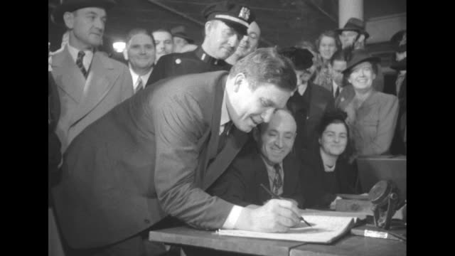 election 1940 / cu mr and mrs wendell willkie at polling place / willkie signs in with register / mrs willkie in voting booth / cu cameramen /... - voting booth stock videos & royalty-free footage