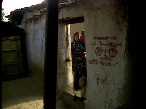 election campaigning; women looking through doorway of hut with stencil of bike on wall boys washing bike in river girls washing pots in river - stencil stock videos & royalty-free footage