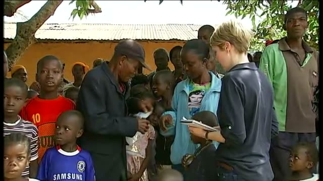 Election violence causes twenty thousand refugees to flee to Liberia Group of adults and children Denis Sohou showing ITN reporter his Ivory Coast...